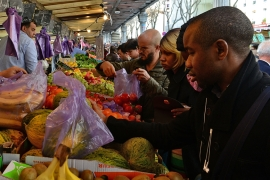 A man buys fruit at the Marche Barbes, the outdoor market located in the 18th arrondissement of Paris as normal life resumes in the area on November 18  [Photo by Frederic T Stevens/Getty Images]