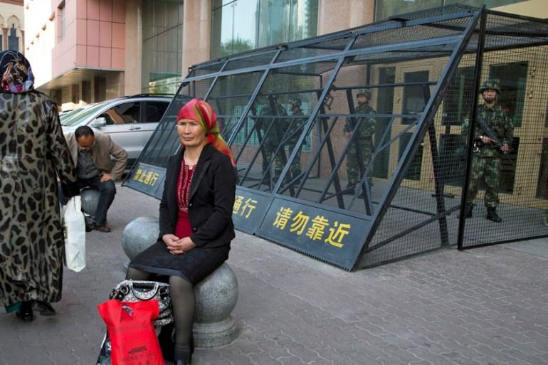 Seorang wanita Uighur beristirahat di dekat kandang yang melindungi polisi paramiliter China yang sedang bertugas di Urumqi di wilayah barat laut China, Xinjiang [File: Ng Han Guan / AP Photo]