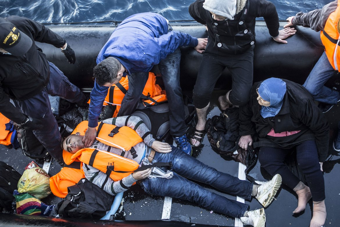 A crew member checks the pulse of an unconscious man lying in the bottom of the boat. [Anna Pantelia/Al Jazeera]