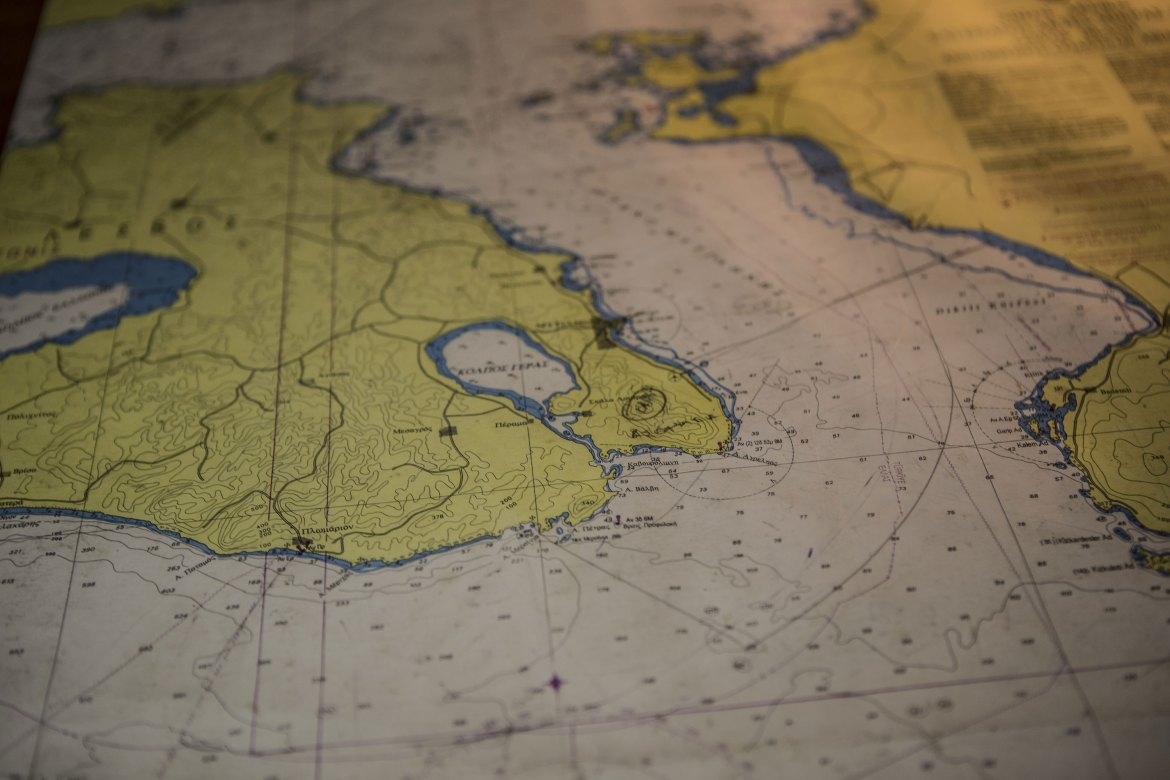 A map of the sea around the port of Mytilene is at hand on the patrol boat's bridge. [Anna Pantelia/Al Jazeera]