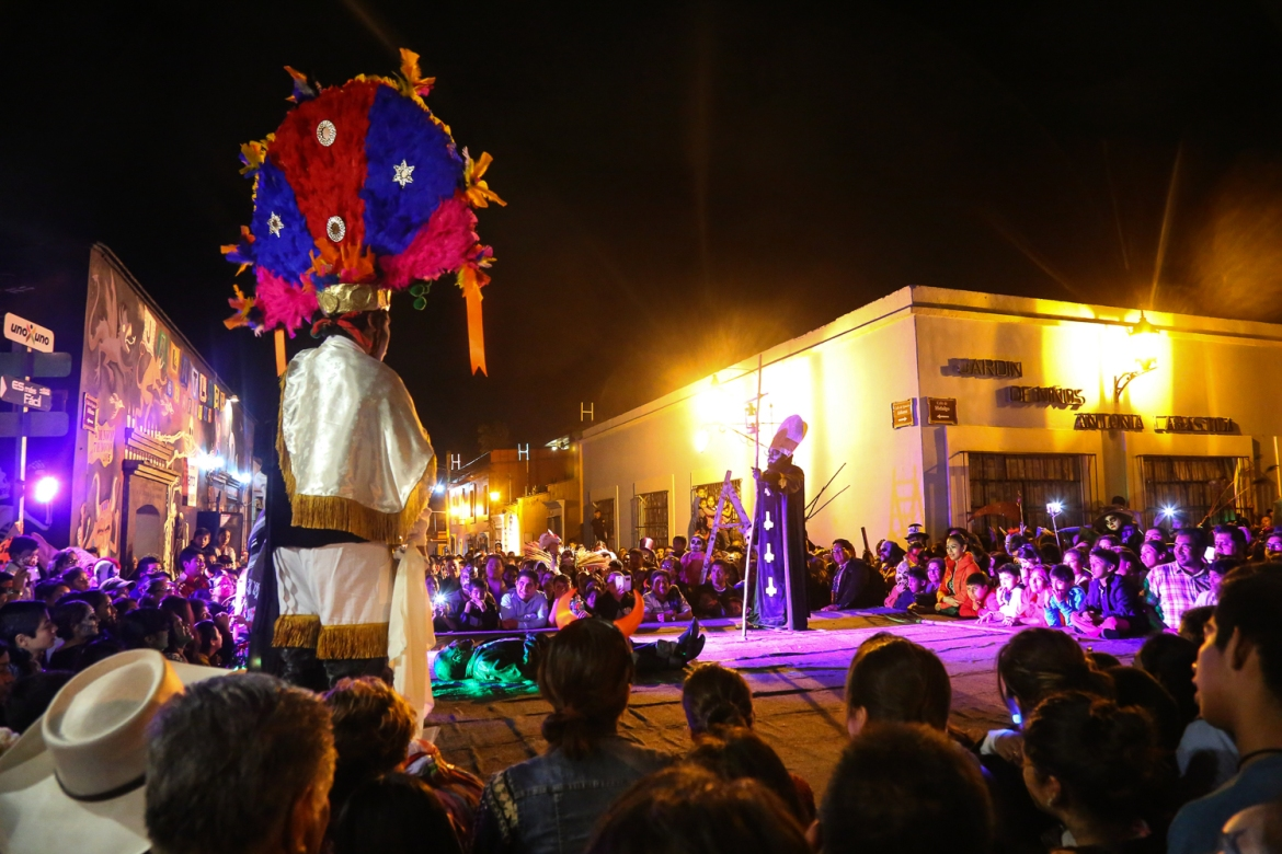 Thousands gather at the beginning of the comparsa, a carnival like event that begins with a Day of the Dead theatre performance and then moves in a procession of dance, music and theatre through the city. [Gabbi Campos/Al Jazeera]