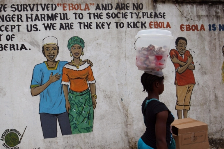 A Liberian woman passes a mural carrying messages about the deadly Ebola virus on a street corner in Monrovia [Ahmed Jallanzo/EPA/File]