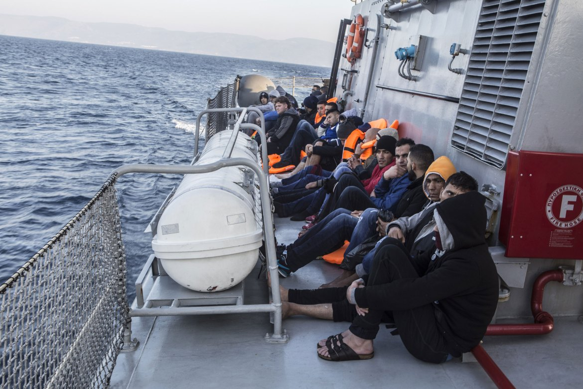 The rescued refugees from Syria and Afghanistan sit on the deck as they are taken to the island of Lesbos where they will be registered. [Anna Pantelia/Al Jazeera]