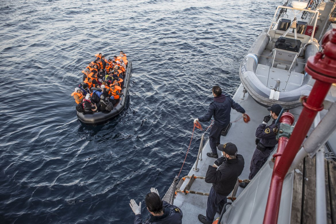 The Agios Efstratios pulls up alongside a stricken boat full of refugees lying idle in the water after its engine cut out. [Anna Pantelia/Al Jazeera]