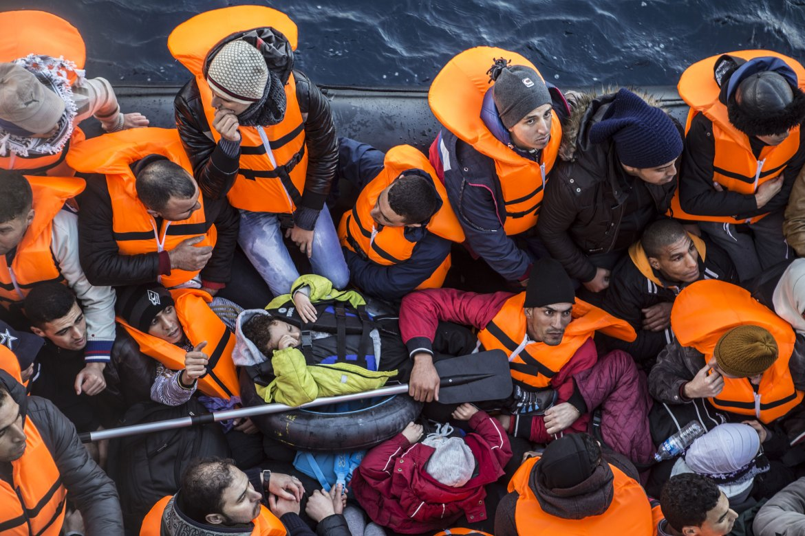 The refugees prepare to leave their inflatable boat that has started to take on water. [Anna Pantelia/Al Jazeera]
