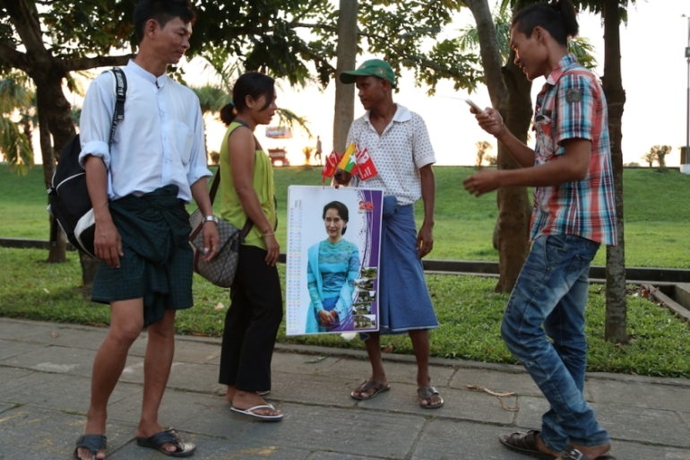 A street vendor in Yangon sells 2016 calendars bearing the image of opposition leader Aung San Suu Kyi [Ted Regencia/Al Jazeera]