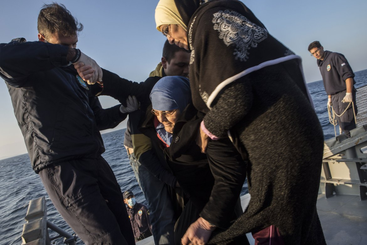 An elderly woman barely able to walk is helped onto the deck of the patrol boat. [Anna Pantelia/Al Jazeera]