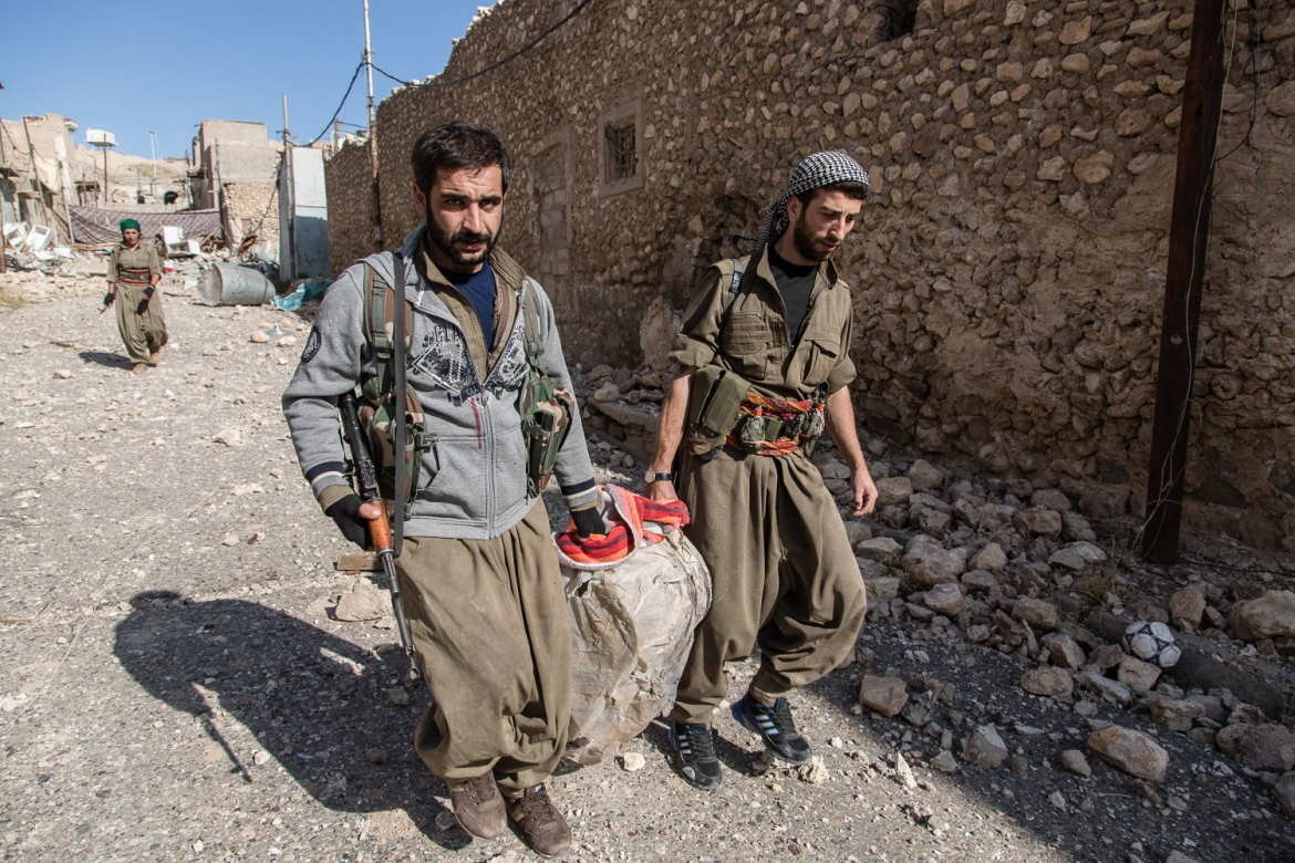 Kurdish fighters carry an improvised explosive device found in one of the homes. They are bringing it to their base to be disarmed. [Hawre Khalid/Al Jazeera]