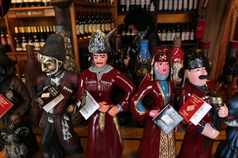 Bottles of Georgian wine decorated with Georgian national costumes at a wine market in the centre of the capital, Tbilisi [Zurab Kurtsikidze/EPA]