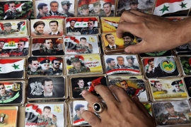 A Syrian vendor arranging pins displaying portraits of Assad with Hezbollah leader Hassan Nasrallah [Getty]