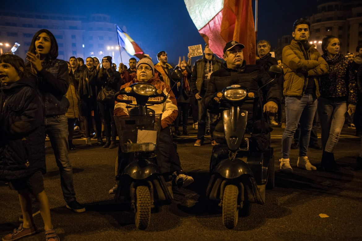 A couple in wheelchairs attend to the protests. [Ioana Moldovan/Al Jazeera]