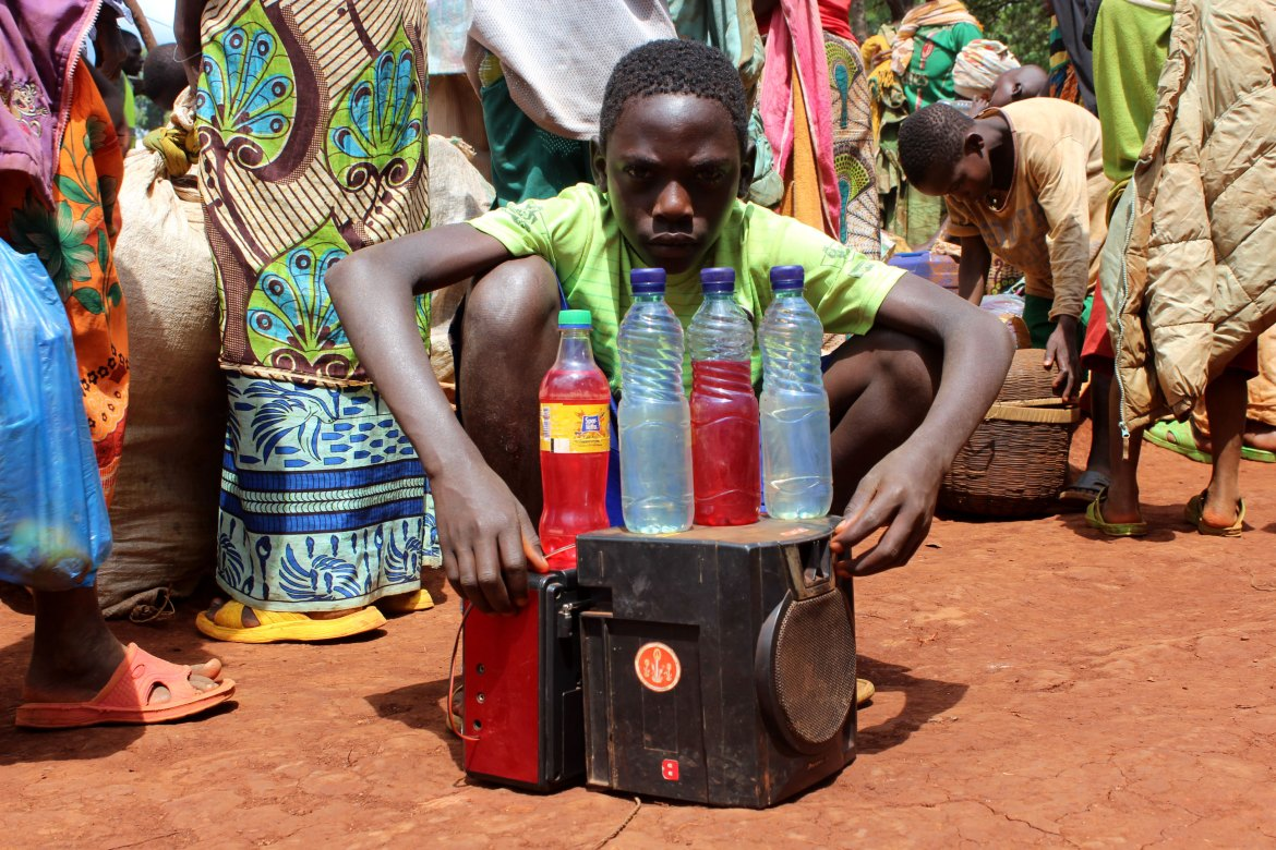 A young boy sits by a speaker and radio he brought along from Burundi. [Tendai Marima/Al Jazeera]