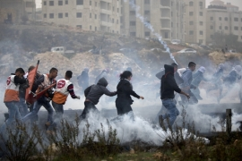 Palestinian protesters run from tear gas during clashes with Israeli forces near the Qalandiya refugee camp last month [File: Majdi Mohammed/AP]