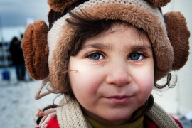 A refugee child waits in the cold in a transit centre in Macedonia [Mona van den Berg/Al Jazeera]