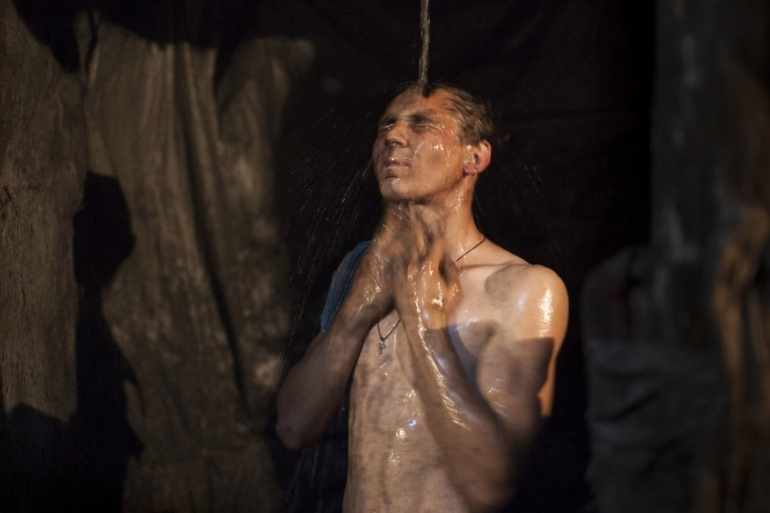 Eighteen-year-old Marek takes a shower after his eight-hour night shift in an illegal mine in Davidovka [Janos Chiala and Tali Mayer/Al Jazeera]