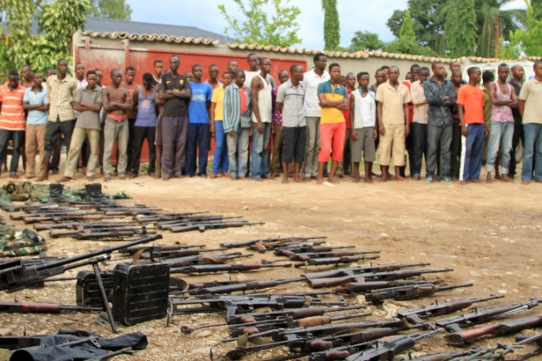 Suspected fighters are paraded before the media by Burundian police near a recovered cache of weapons in the capital Bujumbura, [Reuters]