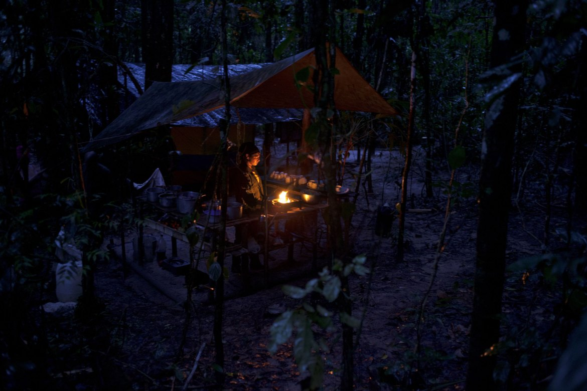 A FARC rebel preparing breakfast in the pre-dawn light. At night, lights are not permitted to avoid being detected. Some rebels dig underground shelters to be able to read. [Fabio Cuttica/Al Jazeera]