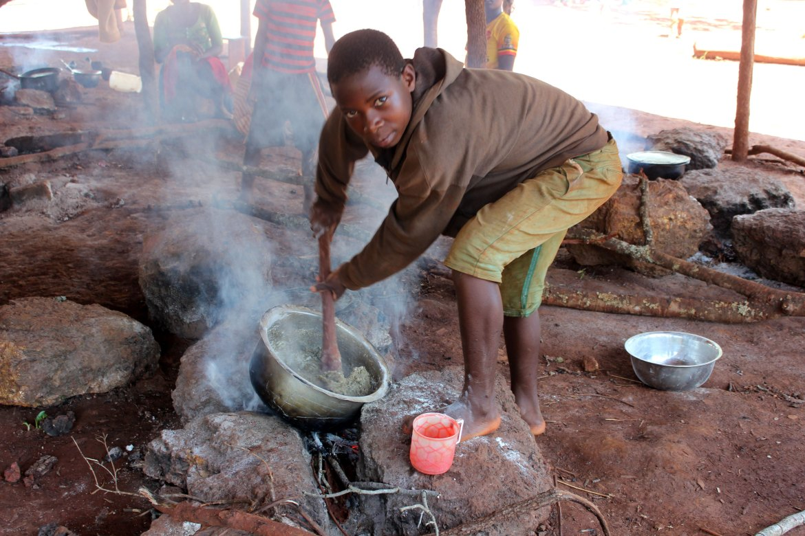 A young boy cooks ugali - a stiff porridge made from maize meal - with ground cassava leaves mixed in, over a communal fire in Nduta camp. [Tendai Marima/Al Jazeera]