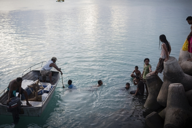 Men in a dingy ask to be pulled back to the break wall by young people swimming in the Betio jetty during the late afternoon [Conor Ashleigh/Al Jazeera]
