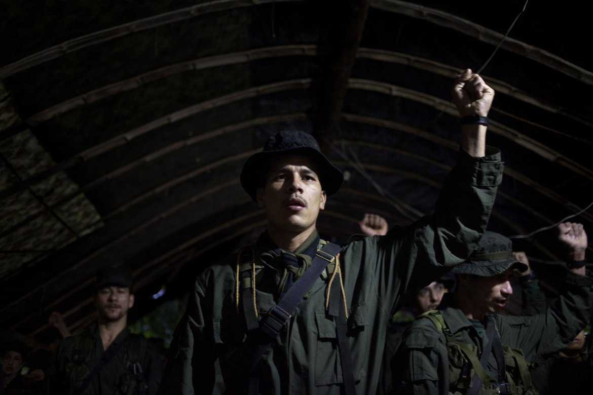 The morning call is issued at 4:50am in FARC camps. After the exercises, rebels gather under tents to sing the organisation's hymn. The group was founded in 1964 to fight on behalf of poor farmers and against what they see as a ruling corrupt and violent elite. [Fabio Cuttica/Al Jazeera]