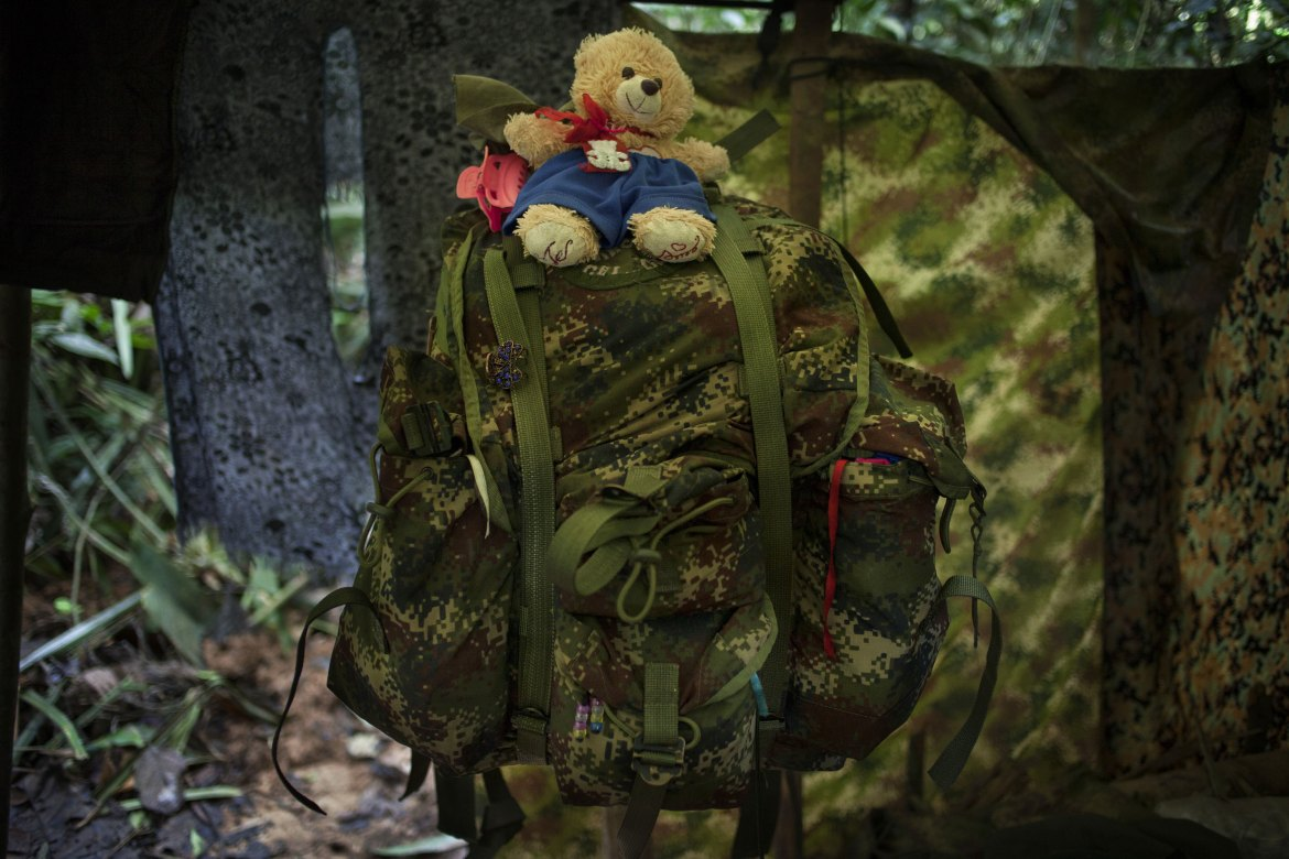 A teddy bear decorates a rebel's backpack. Living on the move in difficult conditions, the rebels have few belongings besides their basic provisions. [Fabio Cuttica/Al Jazeera]