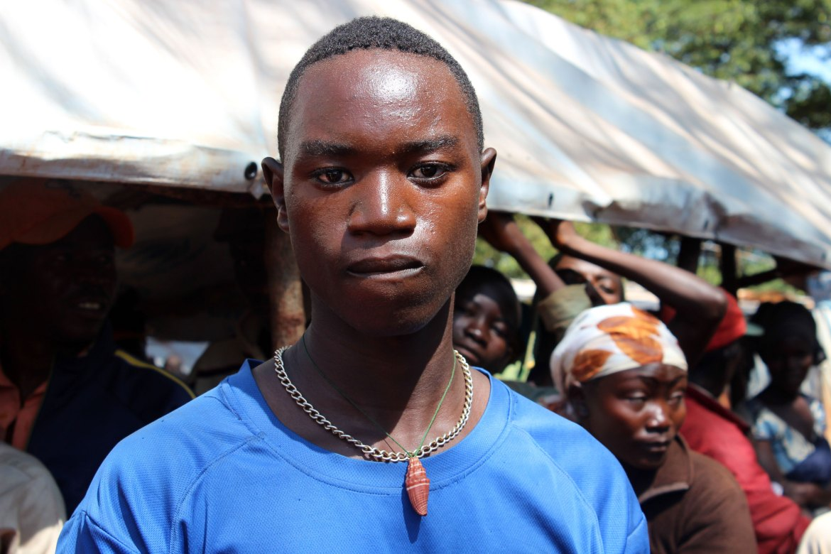 Celest Nimpaye, 18, is a high school student. He lived in the pro-government neighbourhood of Kamenge in Bujumbura, the capital, before coming to Tanzania. His older sibling who stayed behind, gave him a shell necklace as a charm 'for protection' on his journey. [Tendai Marima/Al Jazeera]