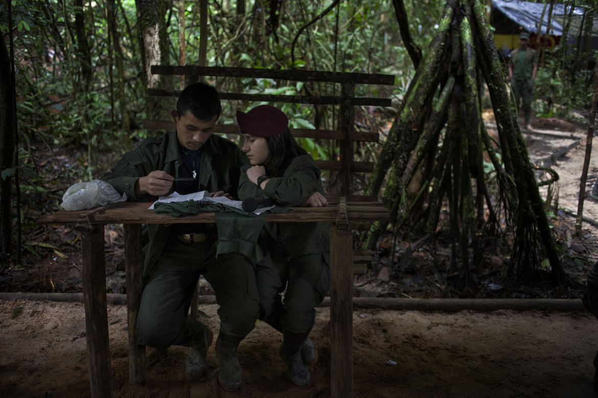Many fighters require basic education. FARC is setting up mathematics and grammar classes for those in need. In the photo, 19-year-old rebel Laura goes over her notes with an associate. She joined the FARC at 15 when her father was killed by paramilitaries for his leftist sympathies. [Fabio Cuttica/Al Jazeera]