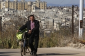 A man is seen pushing his bicycle in an area adjacent to the Waer neighborhood in the central city of Homs, Syria [AP]