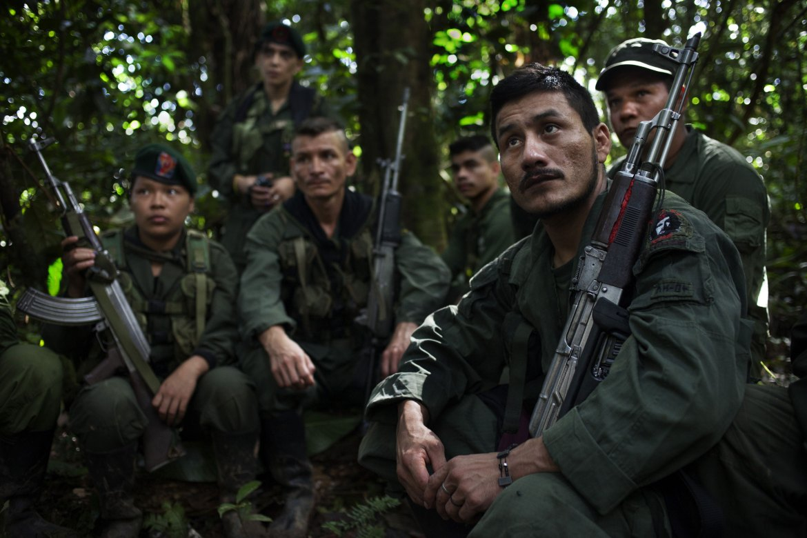 Fidel listens to a morning briefing while on the move with his associates. Commanders discuss news items with the fighters every morning. This day, they discussed allegations that relatives of Venezuela's President Nicolas Maduro were involved in drug trafficking, which the commander considered to be US propaganda. [Fabio Cuttica/Al Jazeera]