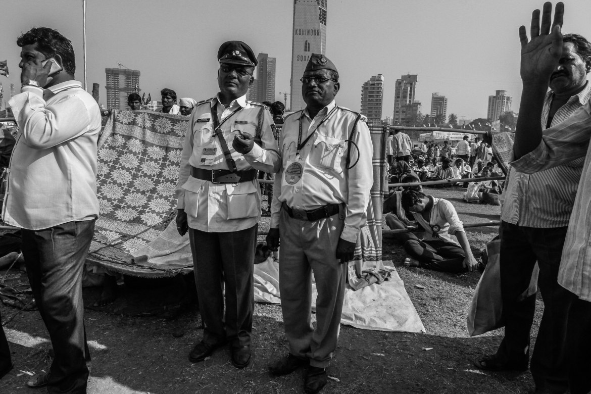 Ashok Kamble, a schoolteacher, and Ananda Bhirje, a retired government employee, volunteer as security guards. They have been volunteering for 35 years. 'More and more people come every year, and the attraction to the place increases by the year,' Kamble said. [Javed Iqbal/Al Jazeera]