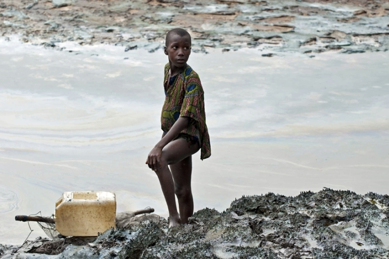 A boy with a fishnet stands on the oil stained bank of a creek near Goi, Nigeria [File: Martin Van Dijl/EPA]