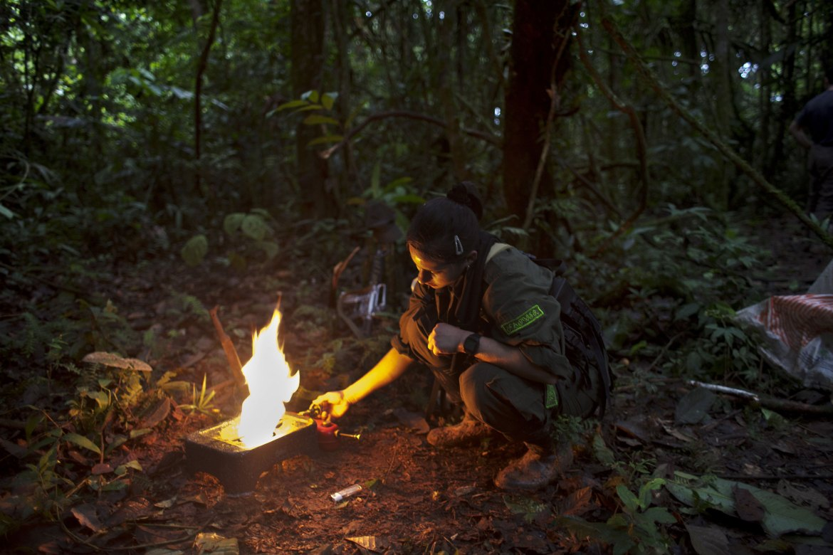 Laura starts a camp stove at dawn. In recent years, FARC has usually operated with smaller units. They pitch a new camp almost every night to avoid detection by the military and avoid being hit by air strikes. [Fabio Cuttica/Al Jazeera]