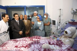 Tunisian President Zine El Abidine Ben Ali visits Mohamed Bouazizi, right, the protester who set himself alight during a demonstration against unemployment, at a hospital in Ben Arous near Tunis on December 28, 2010. [Tunisian Presidency Handout/Reuters]