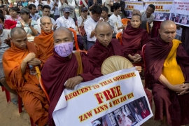 Buddhist monks display placards of two Myanmar labourers sentenced to death in Thailand [Gemunu Amarasinghe/AP]