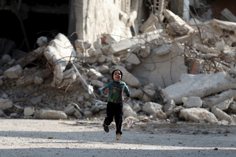 A boy runs in front of damaged buildings in the Douma neighbourhood of Damascus, Syria [Bassam Khabieh/Reuters]