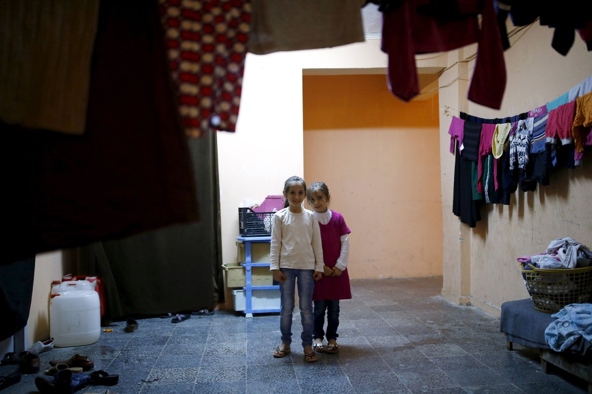 Syrian refugee Ilaf Hassun (left), 9, and her sister Bera, 7, pose at the Yayladagi refugee camp. [Umit Bektas/Reuters]