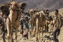 Smugglers carry oxygen cylinders on their camels' backs on a road cutting through the mountains [Taha Saleh/Al Jazeera]