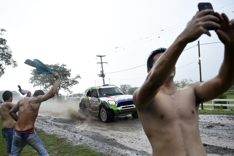 Spectators cheer and take selfies at a dangerous spot at the Dakar Rally [AFP]