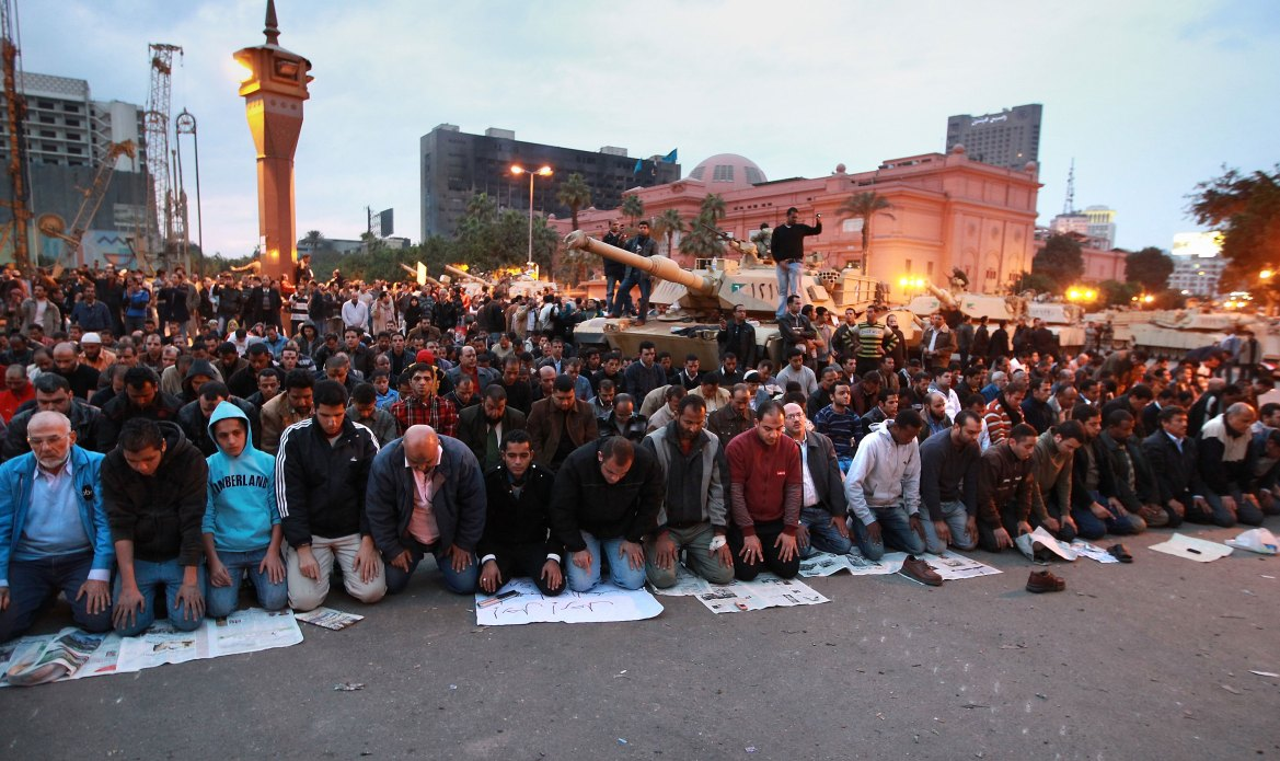 People pray in front of army tanks in Tahrir Square on January 30. [Peter Macdiarmid/Getty Images]