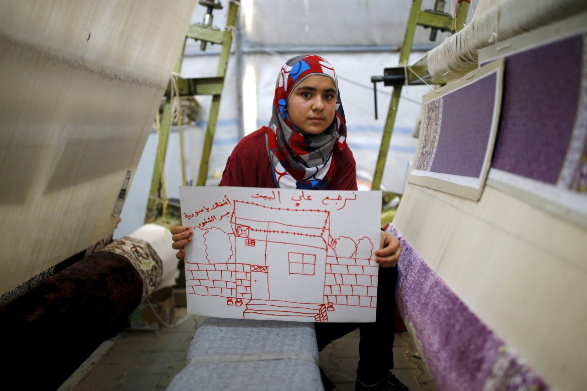 "Meryem Mahmo, 14, shows a drawing of her home during a carpet weaving workshop in Midyat refugee camp in Mardin province, Turkey. The Arabic writing on the picture reads: ""Let's return home. I miss you Syria."" [Umit Bektas/Reuters]"