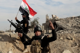 Iraqi security forces raise an Iraqi flag near the provincial council building in central Ramadi [AP]