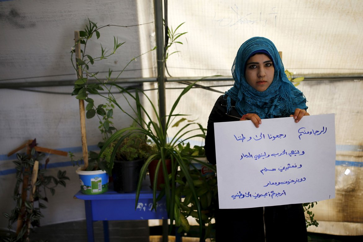"Esma El-Gureyb, 18, holds a paper bearing writing in Arabic that reads: ""My request to you is, return us back to our homeland. Let the war and destruction end; Let us live in peace, without fear and devastation. I beg you: Return me to my homeland."" At the Midyat refugee camp in Mardin province, Turkey. [Umit Bektas/Reuters]"