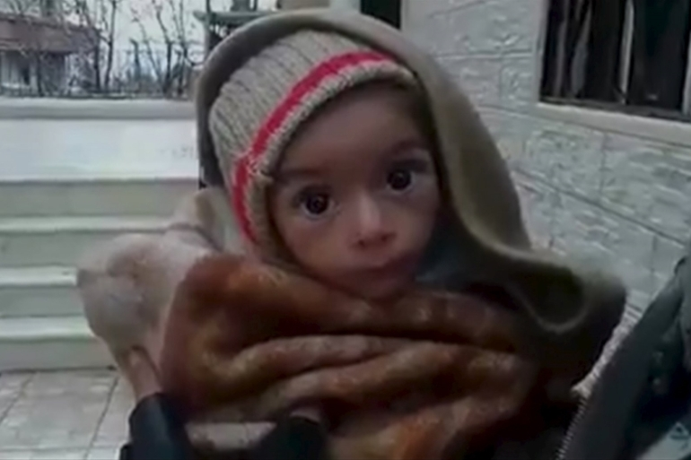 A toddler is held up to the camera in this still image taken from video said to be shot in Madaya on January 5 [REUTERS]