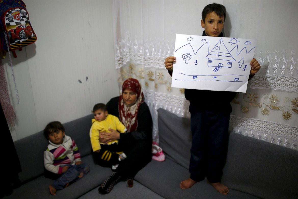Ahmet Cemal, 12, shows a drawing of home as his mother and his two brothers sit next to him in their tent in Nizip refugee camp in Gaziantep province, Turkey. [Umit Bektas/Reuters]