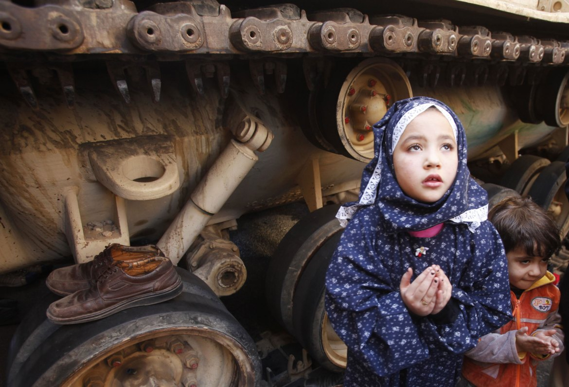 A girl attends Friday prayers in front of an army tank in Tahrir Square on February 18. [Suhaib Salem/Reuters]