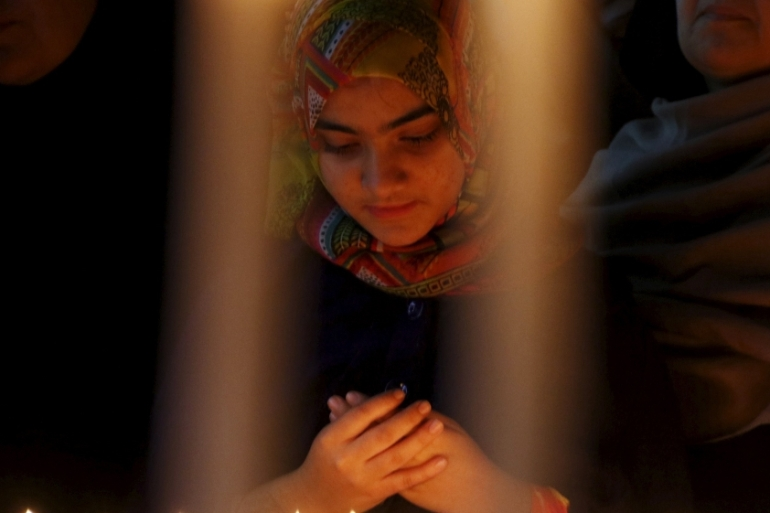 A girl prays for the victims of a militant attack on the Bacha Khan University, during a candle-lit vigil in Peshawar, Pakistan [REUTERS]