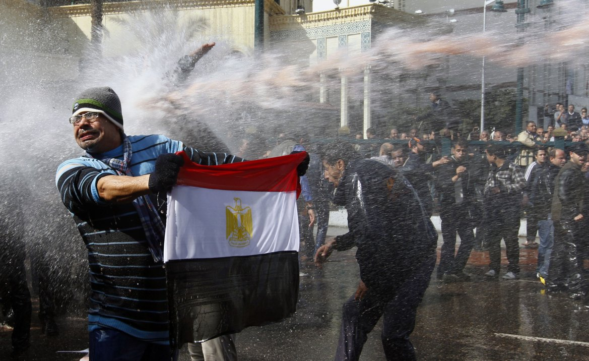 A protester holds an Egyptian flag as police use water cannon during clashes in Cairo on January 28. [Yannis Behrakis/Reuters]
