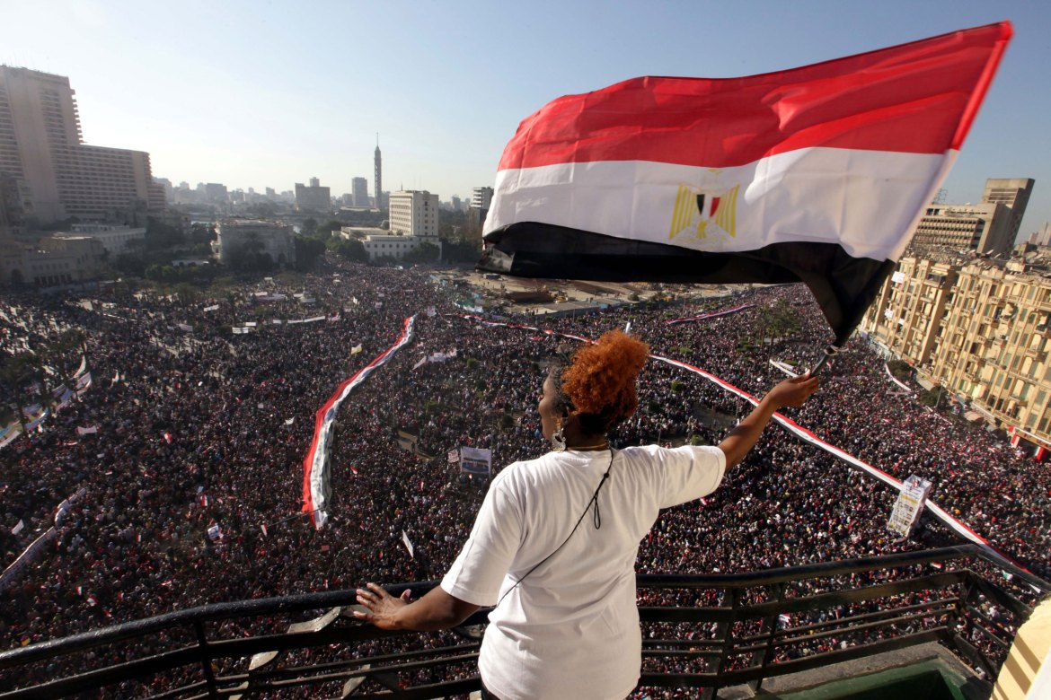 A woman waves an Egyptian flag from a balcony as tens of thousands gather in Tahrir Square on February 18. [Khaled Elfiqi/EPA]
