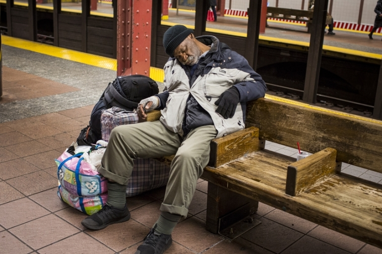 A homeless person sleeps on a subway bench at the 34th Street station in Manhattan, New York City [Edu Bayer/Al Jazeera]