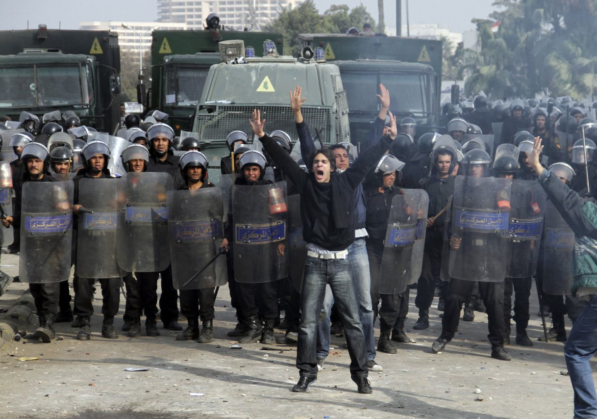 A protester shouts in front of anti-riot police who block a bridge in Cairo on January 28. [Ahmed Ali/AP]